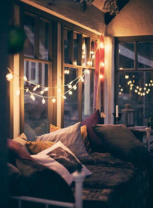Une véranda cosy avec un canapé et des guirlandes lumineuses