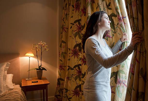 Jeune femme qui change les rideaux dans la chambre d'une maison de retraite
