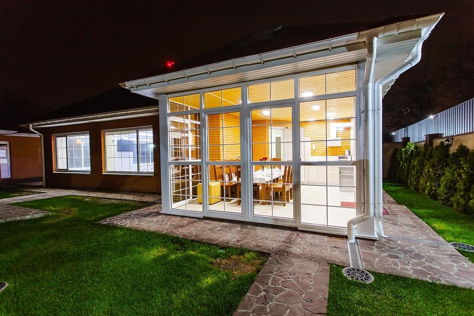 Véranda entièrement vitrée accolée à une maison
