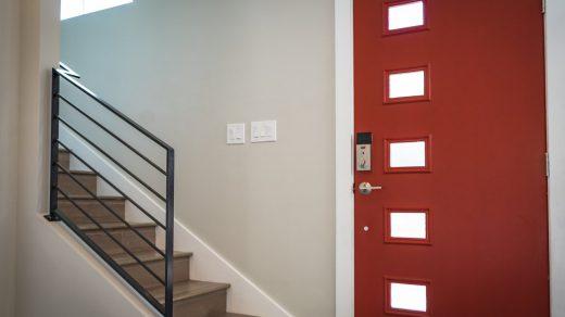 escalier à côté d'une porte d'entrée rouge